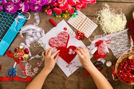 stitching: Materials and tools for hand decoration for Valentines Day on a sacking. Female hands making red heart. Love and valentine concept.