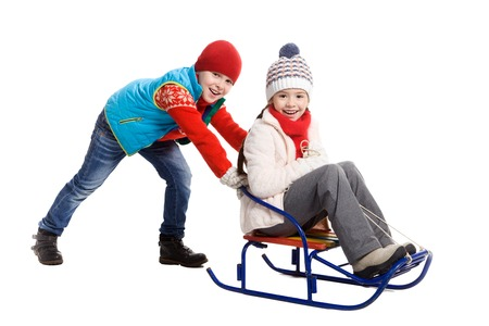 young lady: Little girl and baby boy enjoying a sleigh ride. Child sledding. Toddler kid riding a sledge. Children play in snow. Outdoor winter fun for family Christmas vacation. Stock Photo