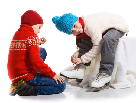 niño en patines: Niño pequeño que ayuda a llevar los patines de niña muy alegre antes de patinaje, aislado en blanco