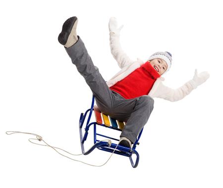 trineo: Niña que disfruta de un paseo en trineo. trineo niño. La niña que cae de un trineo. Los niños juegan en la nieve. diversión del invierno al aire libre para la familia las vacaciones de Navidad.