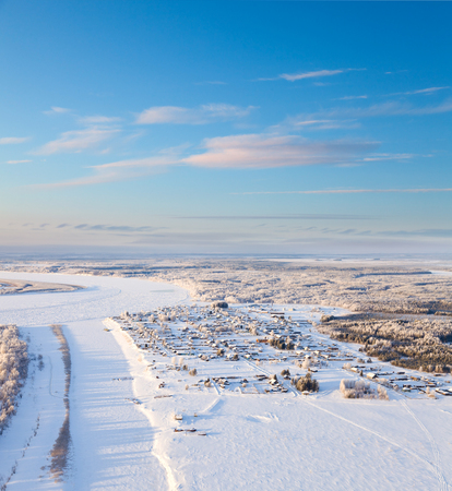 overhand: Aerial view the small village which is located on the banks of the river and near the forest during the winter day. Stock Photo