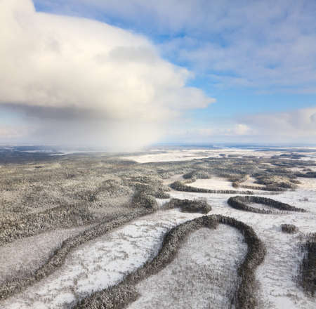 overhand: Aerial view of forest river in cold autumn day during a flight. The weather is cloudy and snowy. Stock Photo