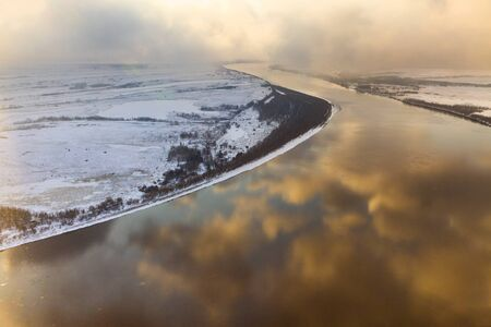 overhand: Snowy clouds coloring by the light of low winter sun are reflected in calm waters of plain river.