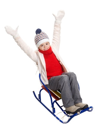 hands lifted up: Little girl enjoying a sleigh ride. Child sledding. Girl riding a sledge. Children play in snow. Joyful girl has lifted up her hands.