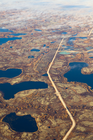 overhand: Aerial view of the tundra in autumn. Marsh with water under cloudy sky. Stock Photo