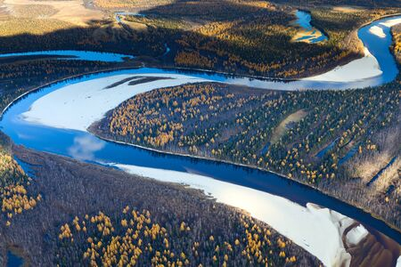 overhand: Aerial view of the tundra in autumn. River is doing loops under clear sky.