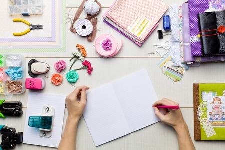 スクラップブッ キング、装飾や手作りアルバムのマスターの手のツールの要素を持つテーブルの平面図です。