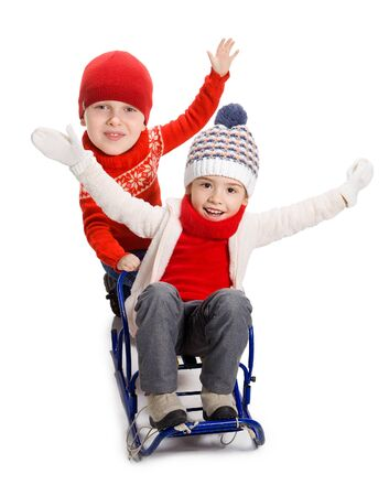 winter fun: Little girl and boy with big heads enjoying a sleigh ride. Child sledding. Comical kids riding a sledge. Children play in snow. Outdoor winter fun for family Christmas vacation.