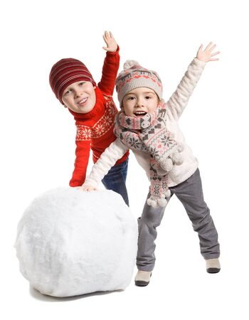 merriment: Funny adorable little children with comical big head making a snowman together, isolated on white