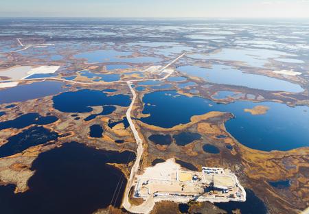 Aerial view of oilfield on impassable swamp area. Stock Photo