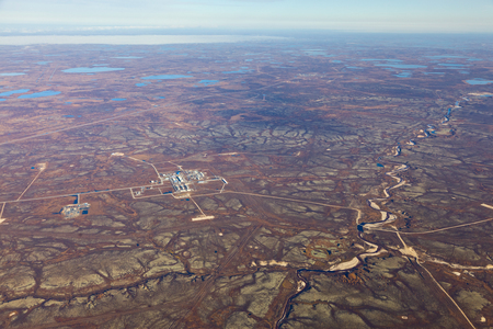 overhand: Aerial view of the oilfield in tundra in autumn. Some gas pipelines running from gas field in tundra. Oil processing plant is located in the foreground. Stock Photo