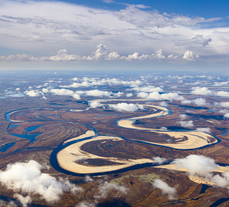 overhand: Aerial view of the tundra in autumn. River is doing loops under cloudy sky.