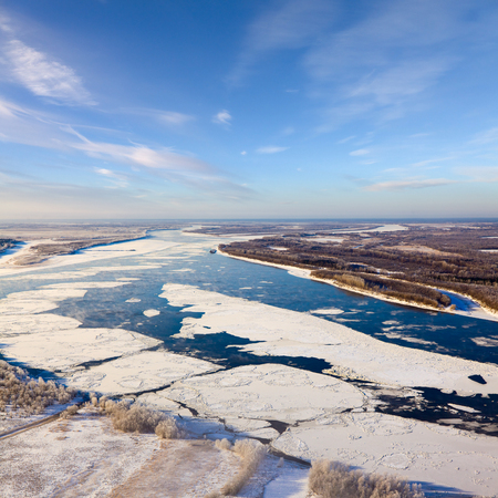 drifting ice: Aerial view of the great river with floating ice floes during sundown. Drifting of ice. Driving of ice. Ice floe.