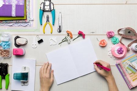 ferraille: Vue de dessus de la table avec des éléments pour le scrapbooking, des outils pour la décoration et albums faits à la main et les mains de maître.