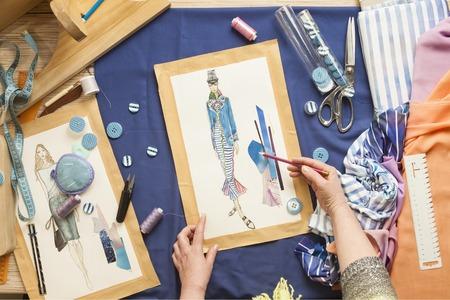 sartorial: Desk designer fashion. Fashion designer starts cutting fabric to create fashionable clothes on the sketches.