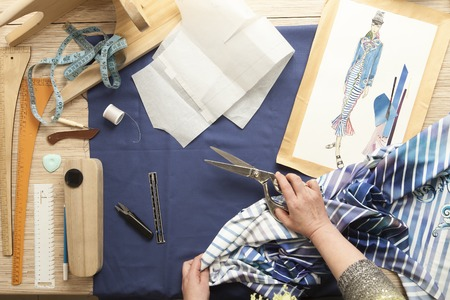 sartorial: Desk designer fashion. Fashion designer starts cutting fabric to create fashionable clothes on the sketches.
