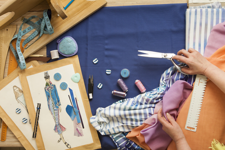 modiste: Desk designer fashion. Fashion designer starts cutting fabric to create fashionable clothes on the sketches.