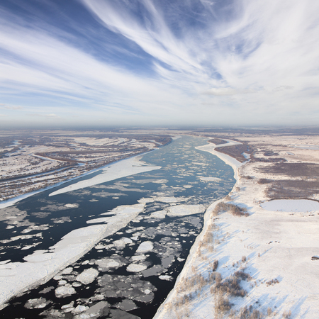 overhand: Aerial view of the great river with floating ice floes during the spring days. Drifting of ice. Driving ice floe.