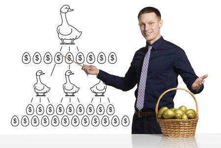 ocas: hombre de negocios joven que muestra el esquema de negocio de éxito. Frente a él está canasta con huevos de oro sobre la mesa. Patos que ponen huevos de oro en el esquema.