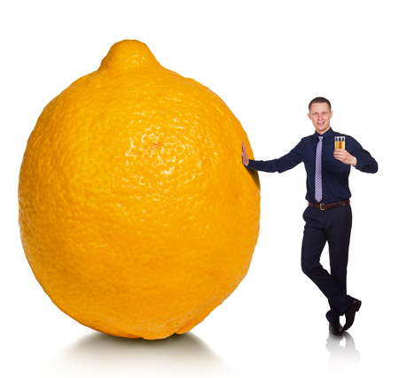 hopefulness: If fate has presented you a lemon, make lemonade. Cheerful young man made from lemon delicious lemonade. Conceptual allegory. Stock Photo