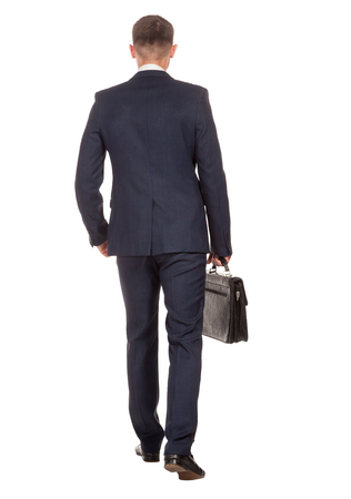 Rückansicht eines Geschäftsmannes, der einen Aktenkoffer halten und nach vorne, isoliert auf weißem Hintergrund zu Fuß