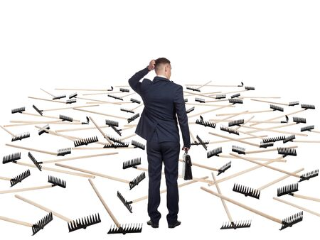 difficult lives: Young businessman in a suit and with a briefcase is undecided before the field that hosts a lot of rakes. He is afraid to move further. Concept of difficulty of deciding.