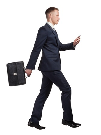 jumping businessman: side view of jumping businessman with his briefcase, watching on the mobile phone on white background Stock Photo
