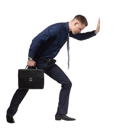 Young Businessman with briefcase trying to move barrier, conceptual photo, isolated on white background.