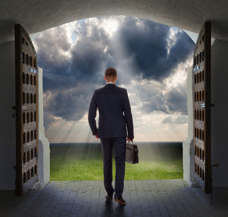 exits: Young businessman exits from gate and moves toward the glowing heavens.