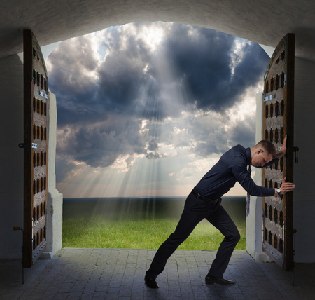 open business: Young businessman is opening to moves toward the glowing heavens. Stock Photo