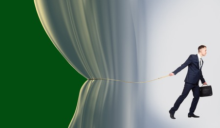 blue curtain: businessman pulling blue curtain to open a green blank background