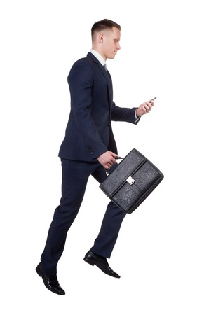 hurrying: side view of hurrying businessman with his briefcase, trying to call by the mobile phone on white background
