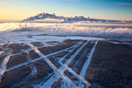 Power station with rising steam from pond to sky in winter season, aerial view.