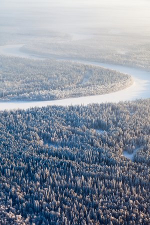 overhand: Aerial view of countryside road which is near forest river during cold winter day. Magnificent hoarfrost is on trees.  A winter forest is in a hard frost. Stock Photo