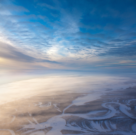 geophysical: The Aerial view the river on snow-covered forest plain in time of cold winter day. Network of seismic tracks of geophysical exploration in Western Siberia, top view