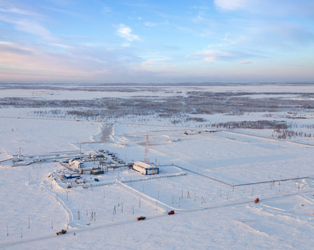 condensate: Aerial view of oil rig at an oil field in Western Siberia in the winter day. This is a station the primary processing of gas condensate. Special transports move to oil field on the road. There is a connected tower, through which passed all the parameters