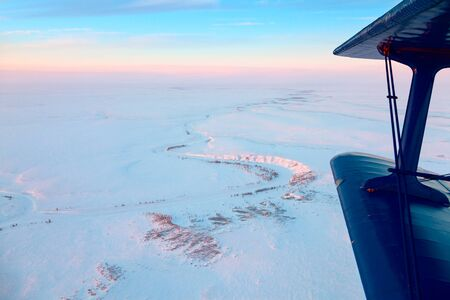 duskiness: Flight above endless tundra in winter Stock Photo