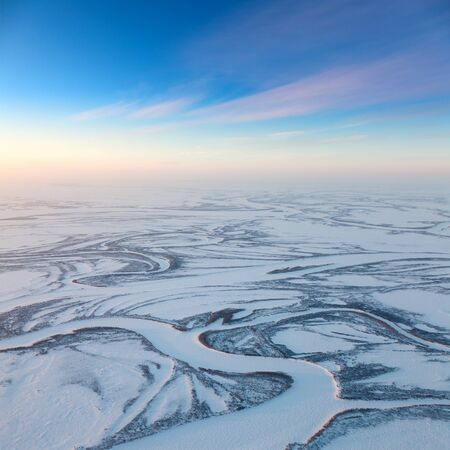 duskiness: Short winter day above frozen tundra river, top view