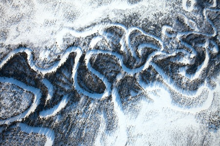 overhand: Aerial view of forest river which is on woodland in the sunny winter day during a flight.