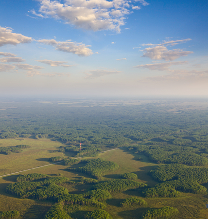 Aerial view over forest area with communications antenna tower in summer Stock Photo