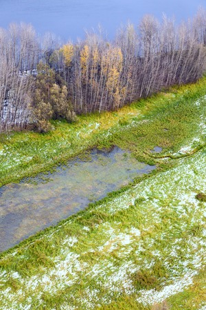 overhand: Top view of meadow on the bank of forest lake after first snowfall in late autumn. Stock Photo