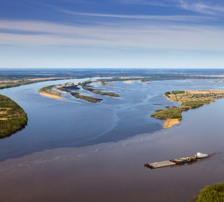 Aerial view of the ship which is pushing barge with vehicle details in the confluence of two rivers during spring