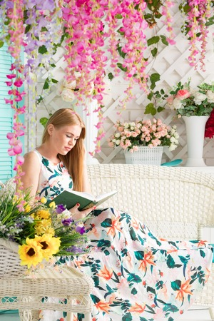 young woman with book in summer terrace