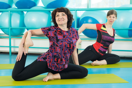 Women doing yoga exercise in the gym Stock Photo