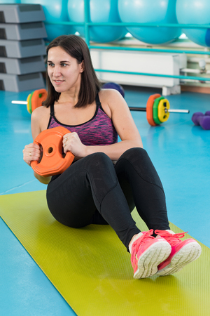 Young woman at the exercising gym
