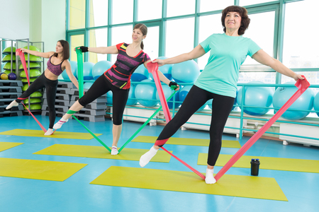 Women doing gym exercises using latex fitness bands Stock Photo
