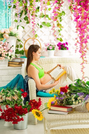 Young pregnant woman reading a book in a summer terrace