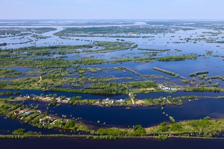Flooded houses in the floodplain of a large river during the spring flood, birds eye view