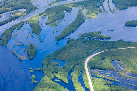 Aerial view flooded forest plains with country road and ferry.