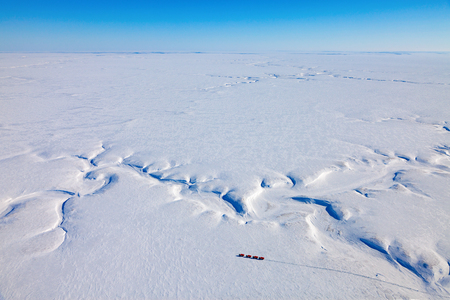 Seismic vibrator Trucks in winter tundra from above